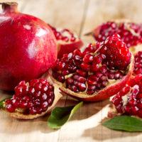 frutto-melograno-intero-aperto-arilli-rossi-traslucidi.