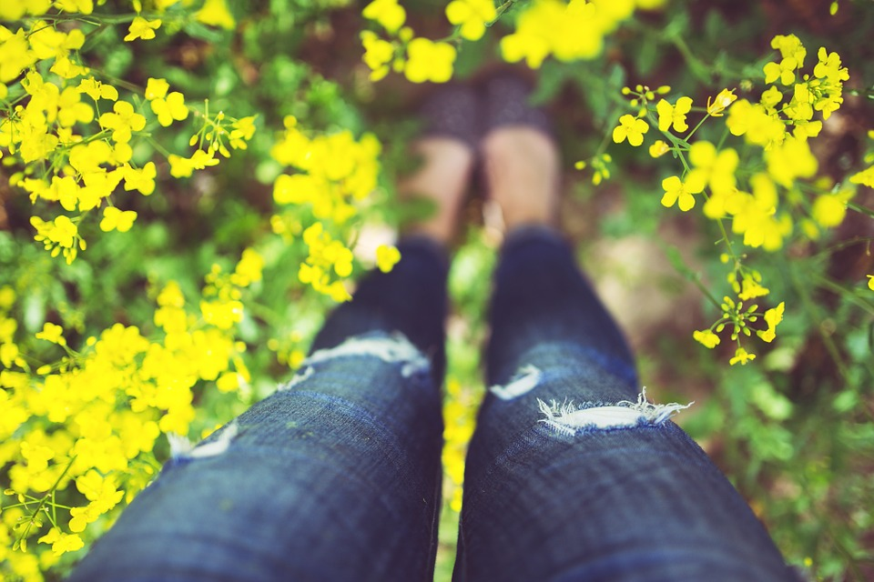 Donna in un campo di fiori gialli - dettaglio delle gambe con i jeans