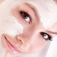 Donna con maschera purificante all'argilla bianca e asciugamano in testa