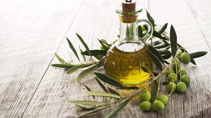Olio EVO - bottiglietta con olio extraverginde d'oliva, circondata da un ramoscello coi frutti