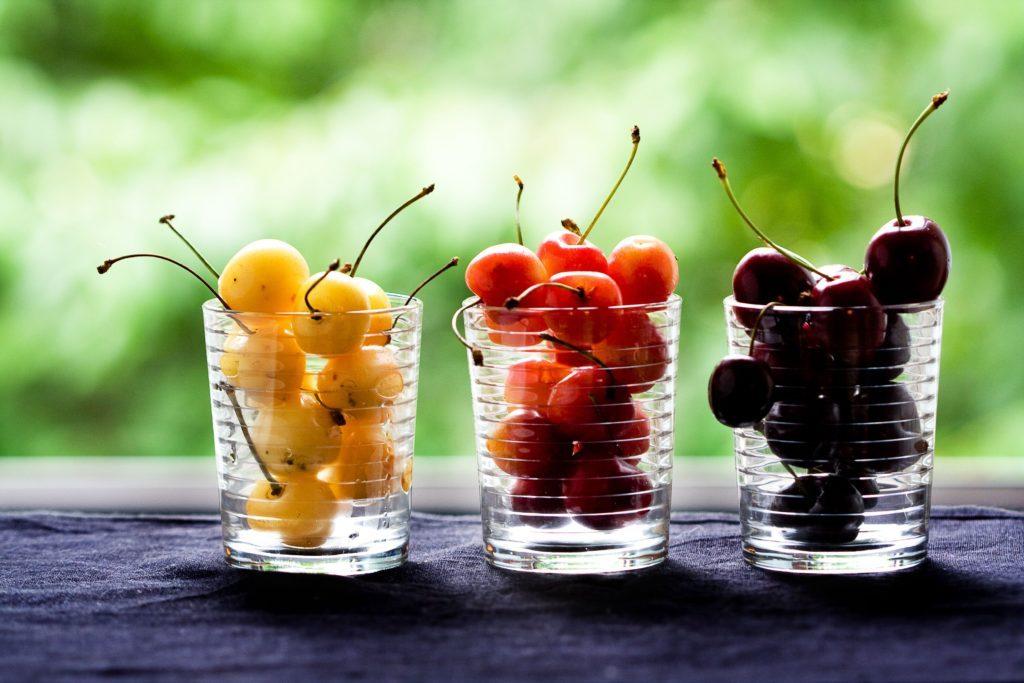 Ciliegie gialle, arancioni e nere distribuite in tre bicchieri di vetro