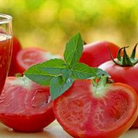 Pomodori in cucina - pomodori interi e affettati insieme a un cicchiere di passata