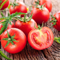 Pomodori rossi maturi, appoggiati sul tavolo di legno.
